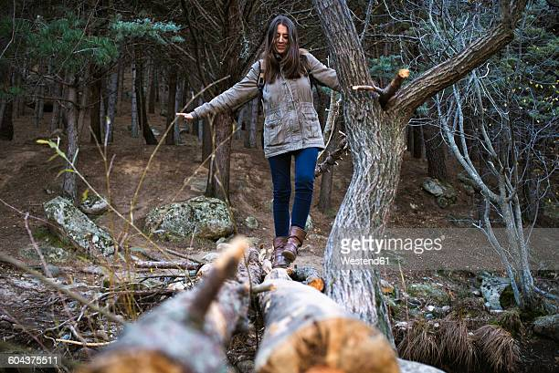 Young woman crossing a bridge made of tree trunks