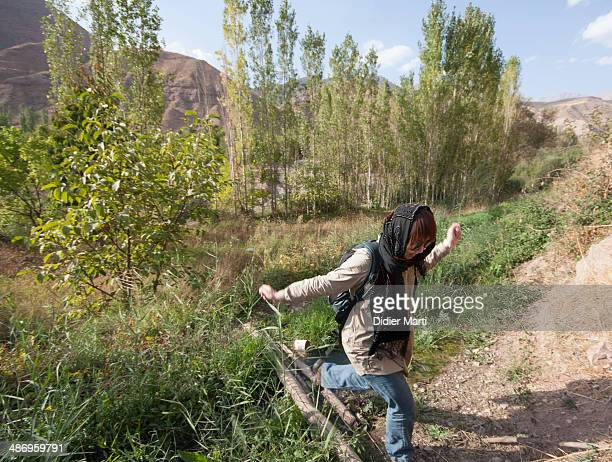 Young woman Crossing a small river in the Alamut valley in Iran