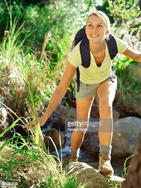 Young woman crossing a stream