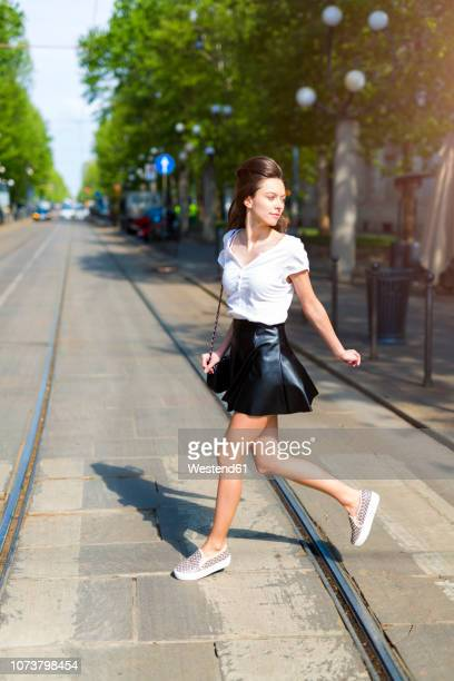young woman crossing a street with tramway tracks in the city - minirok stockfoto's en -beelden