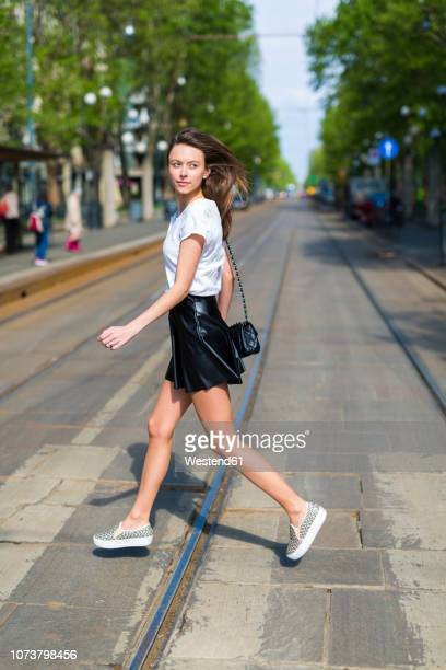 young woman crossing a street with tramway tracks in the city - wind blows up skirt stock pictures, royalty-free photos & images