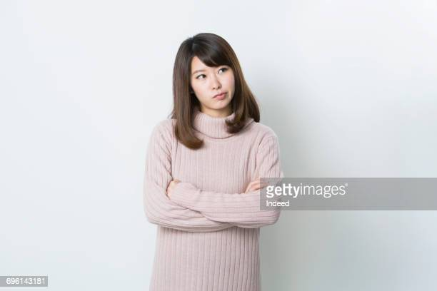 Young woman crossing arms and thinking