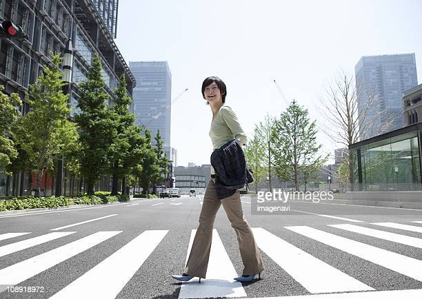 Young woman crossing at crosswalk