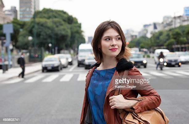 young woman crossing avenue - paso de cebra fotografías e imágenes de stock
