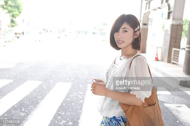 Young woman crossing city street,with smartphone