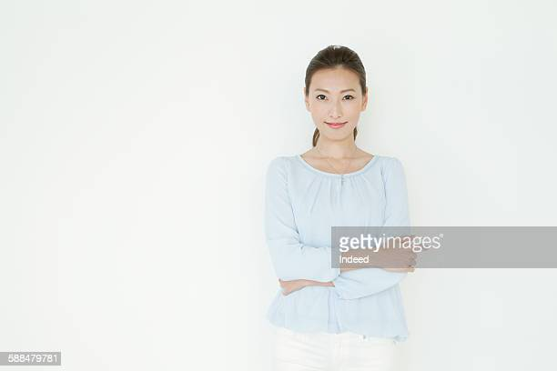 young woman crossing her arms - waist up stock pictures, royalty-free photos & images