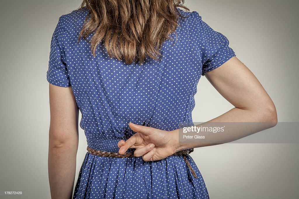 Young woman crossing her fingers behind her back : Stock Photo