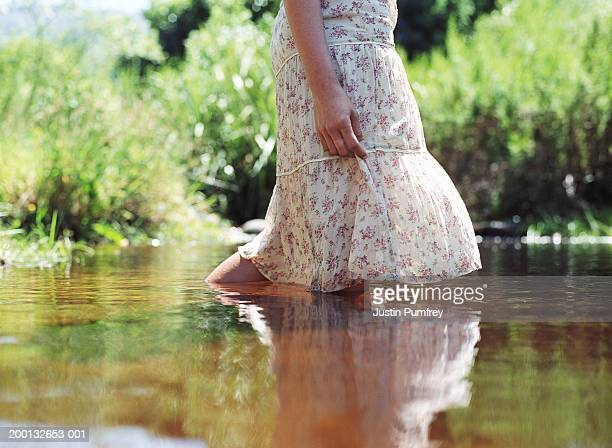young woman crossing stream, wearing floral print dress, mid section - waist deep in water stock pictures, royalty-free photos & images