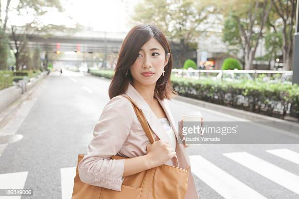 Young woman crossing street,holding coffee