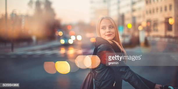 Young woman crossing the street with bicycle
