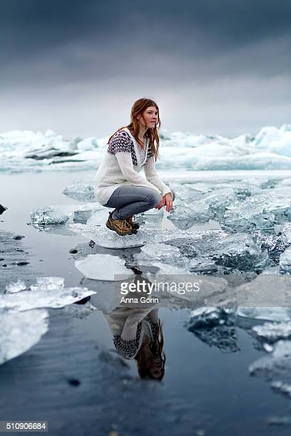 Young woman crouches on iceberg at Jokulsarlon glacial lagoon, reflected in water