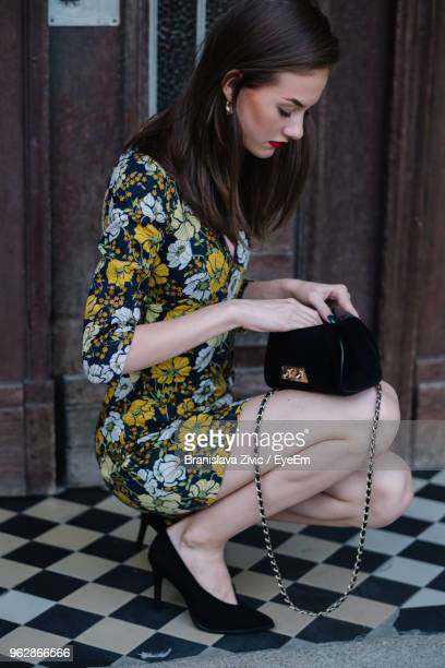 Young Woman Crouching Against Door