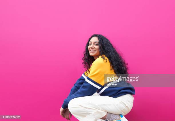 young woman crouching and smiling - colour block stock pictures, royalty-free photos & images
