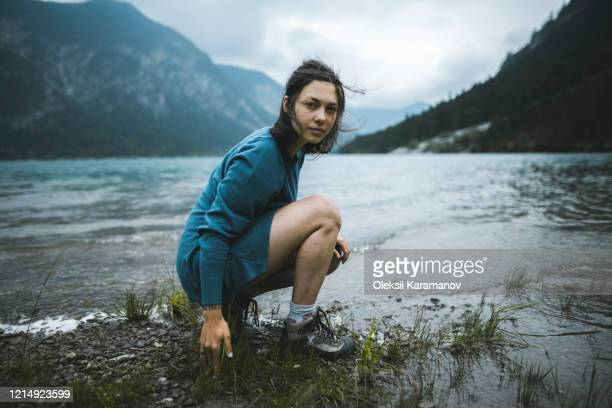 young woman crouching by lake - しゃがむ ストックフォトと画像