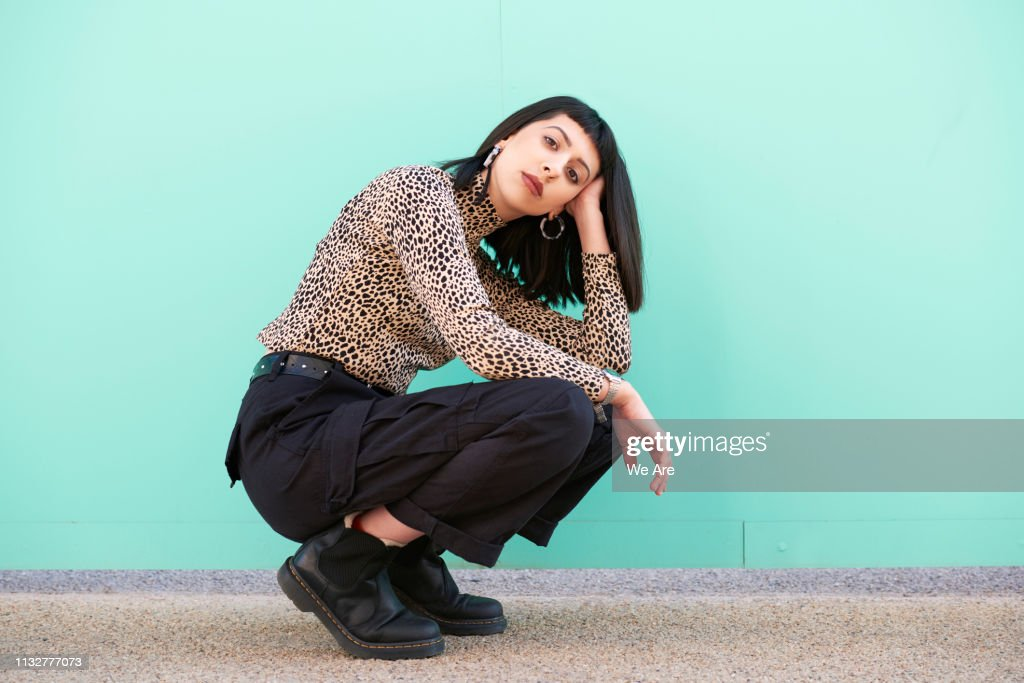 Young woman crouching down in front of blue wall. : Stock Photo