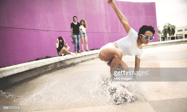 a young woman crouching down on a skateboard to create a water spray. - showing off stock pictures, royalty-free photos & images