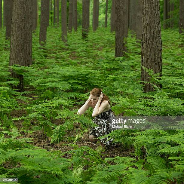 Young woman crouching in forest with head in hands
