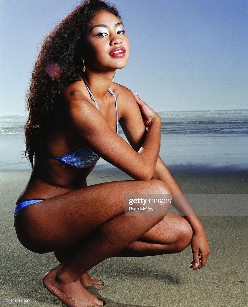Jeune femme Accroupi sur la plage, portrait : Photo