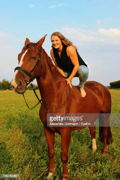 Young Woman Crouching On Horse At Field Against Sky