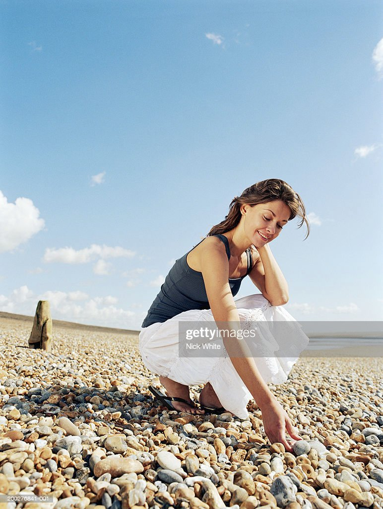 Young woman crouching on pebble beach, picking up pebbles, smiling : Foto de stock