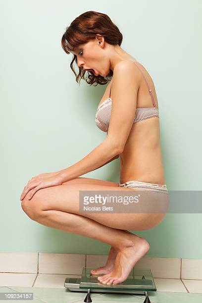 Young woman crouching on scale