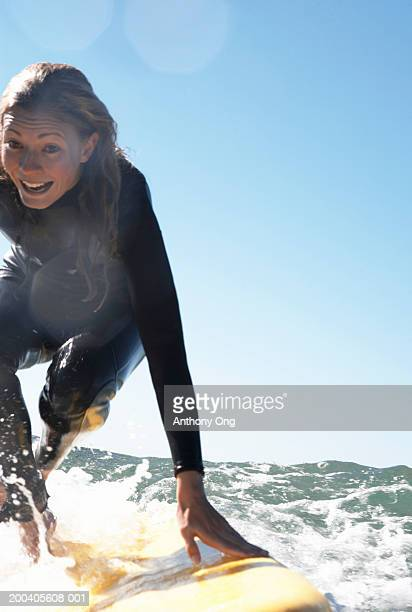 young woman crouching on surfboard in sea, smiling - vertical stock pictures, royalty-free photos & images