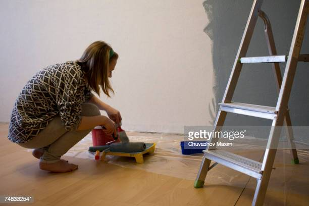 Young woman crouching to prepare grey paint for interior wall at home