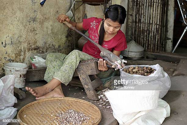 A young woman crushes betel nut on the streets of Mandalay on 25th May 2016 in Myanmar
