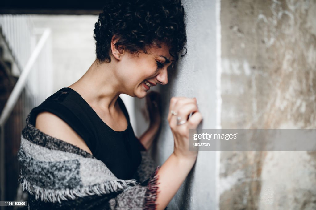 Young woman crying on the stairs : Stock Photo
