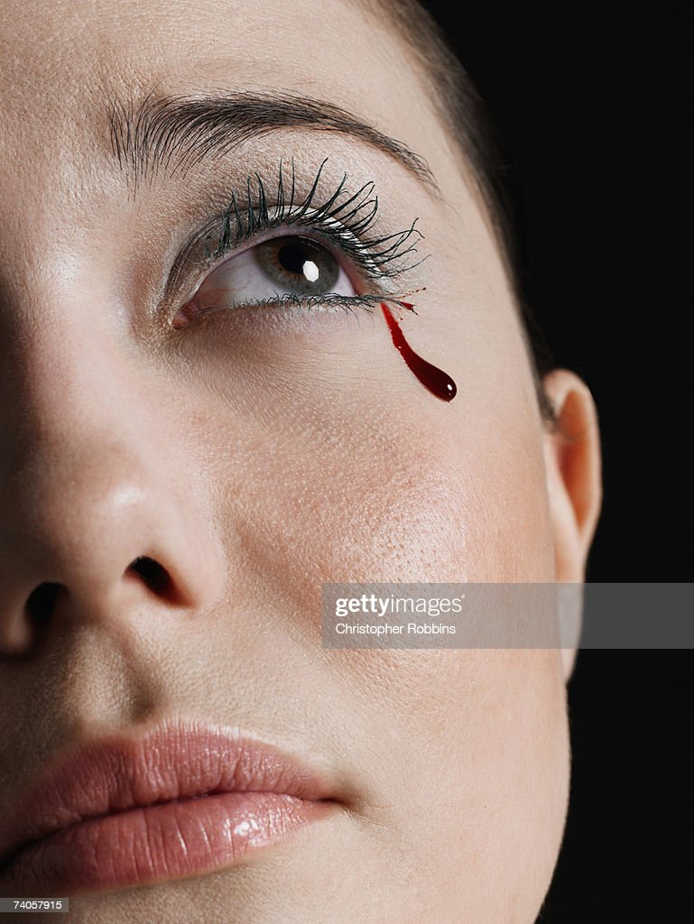Young woman crying tear of blood, close-up of face : Stock Photo