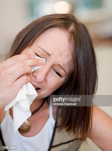 Young woman crying with a tissue