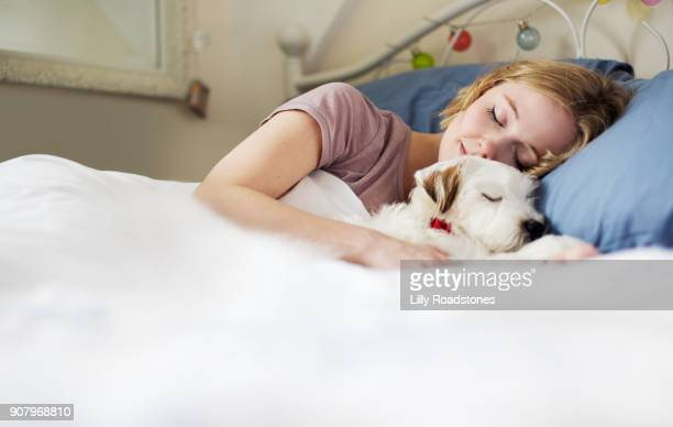Young woman cuddling up to dog in bed