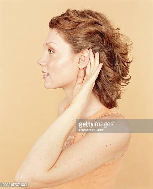 Young woman cupping hand to ear, profile