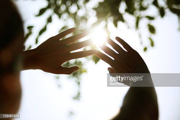young woman cupping hands around sun - sunlight ストックフォトと画像