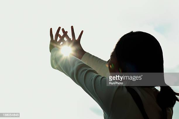 young woman cupping hands around sun - 25 29歳 ストックフォトと画像