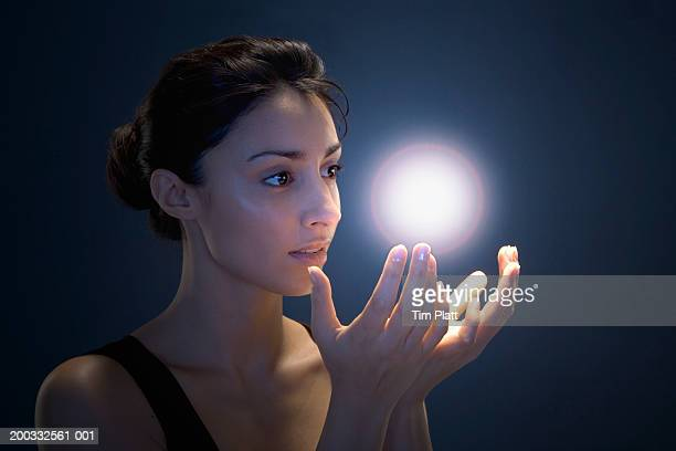 young woman cupping hands beneath glowing orb (digital enhancement) - hands cupped stock pictures, royalty-free photos & images