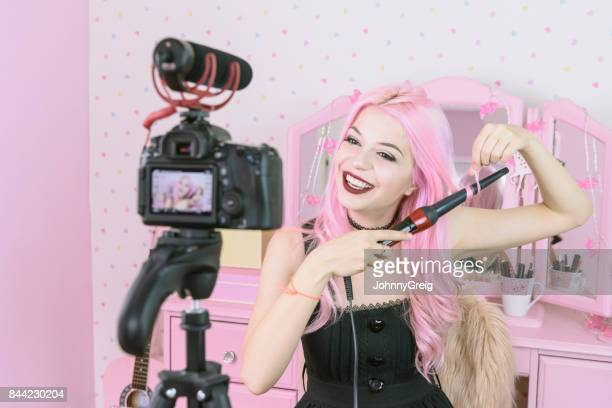 Young woman curling dyed pink hair in her bedroom in front of video camera