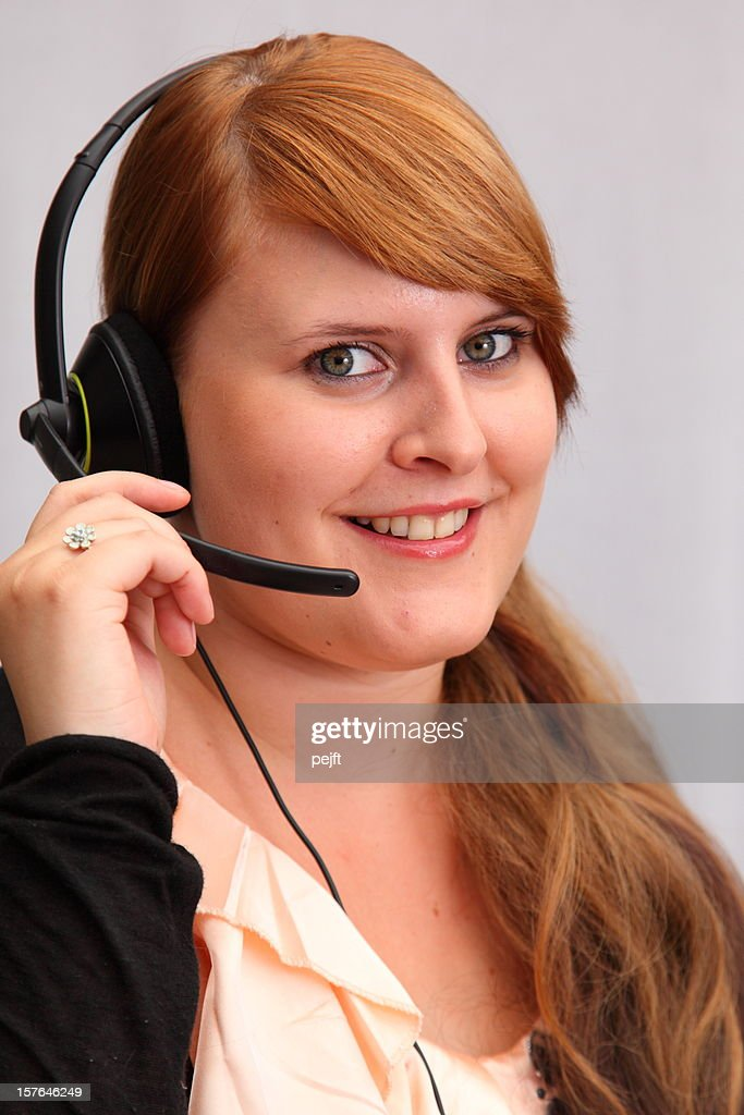 Young woman customer service representative in call center smiling : Stock Photo
