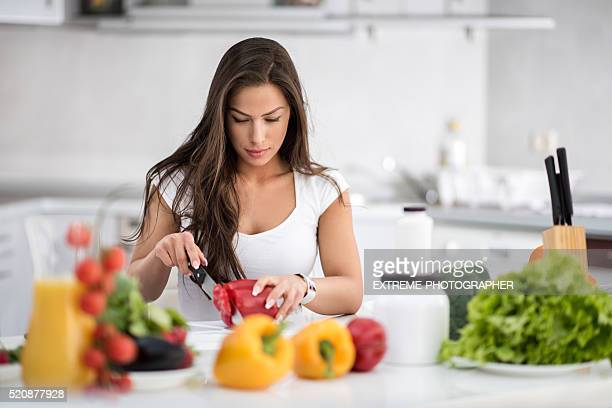 young woman cutting bell pepper - raw food diet stock pictures, royalty-free photos & images
