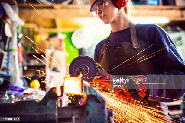 Young woman cutting iron bar in workshop