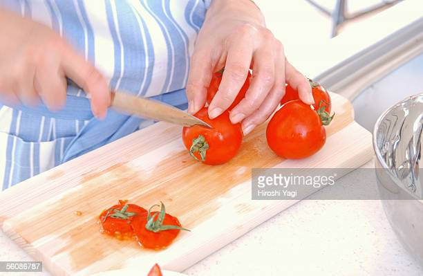 A young woman cutting tomatoes