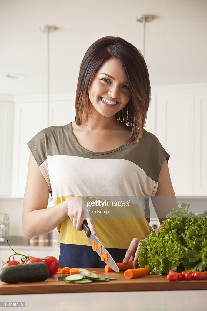 Young woman cutting vegetables : Stock Photo