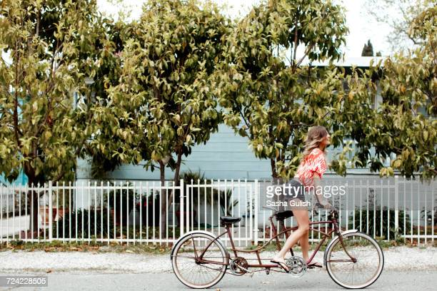 Young woman cycling alone on tandem bicycle along street