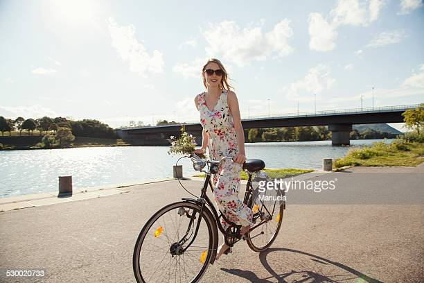 Young woman cycling along riverside, Danube Island, Vienna, Austria