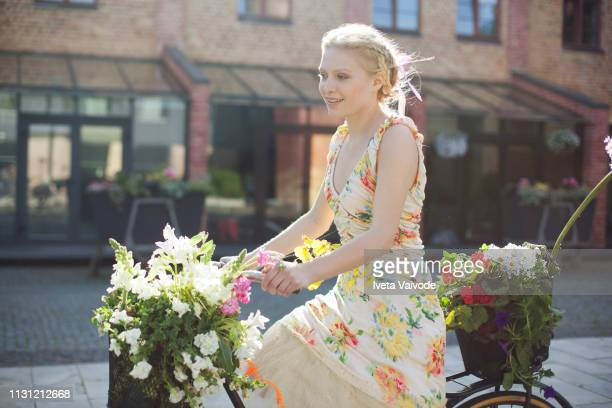 young woman cycling along road, carrying flowers in baskets on bike - floral pattern dress stock pictures, royalty-free photos & images