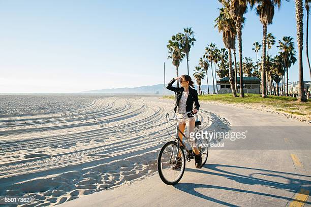 young woman cycling at beach looking out to sea, venice beach, california, usa - los angeles foto e immagini stock