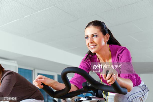 young woman cycling at the gym - izusek stock photos and pictures