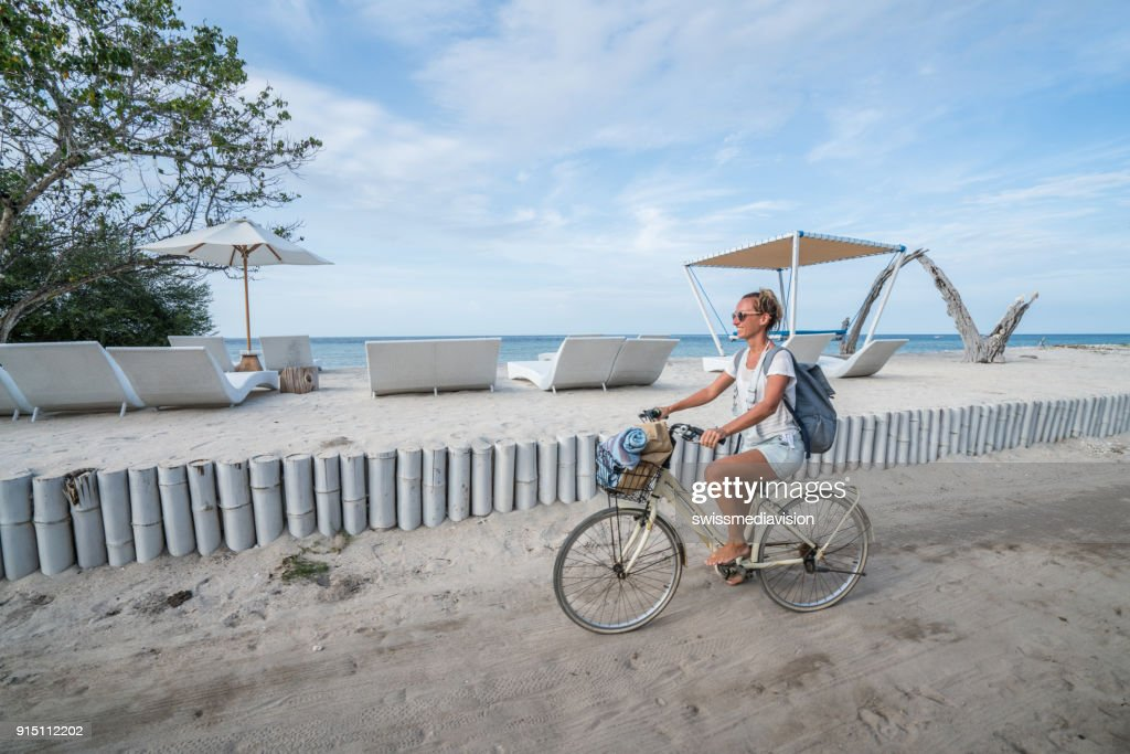 Young woman cycling by the beach in the morning : Stock Photo