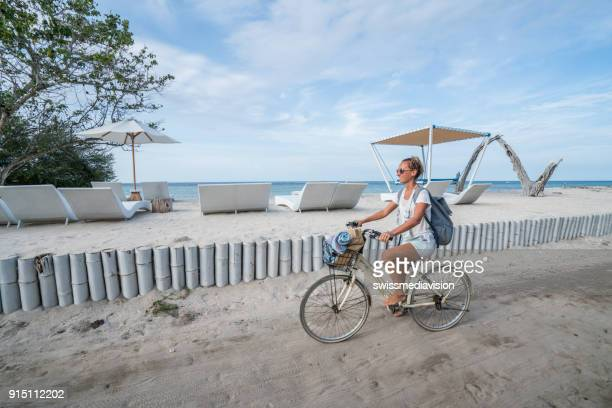 young woman cycling by the beach in the morning - gili trawangan stock photos and pictures