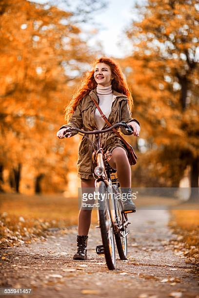 Young woman cycling in autumn.